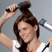 Дівчина сушить волосся феном